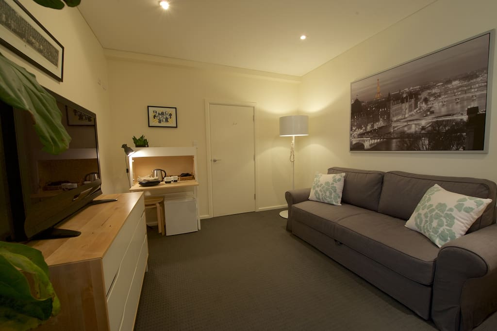 The living room is complete with a bar-fridge, tea and coffee making facilities, a television with free-to-air and Apple TV and Netflix.