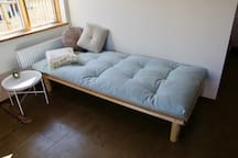 The cosy wooden sofa bed in the living area