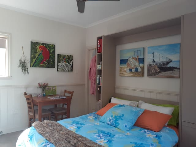 Paintings above the bed are of the historic Shorncliffe pier and and the other is of a sunbather on popular Suttons Beach at Redcliffe.