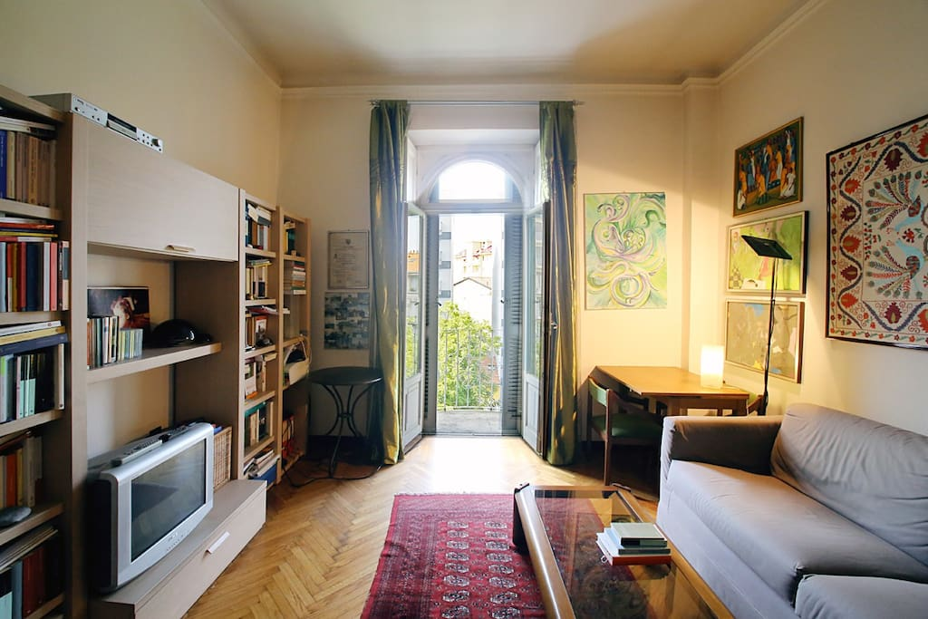 soggiorno con divano letto e libreria fornita di un elevato numero di libri