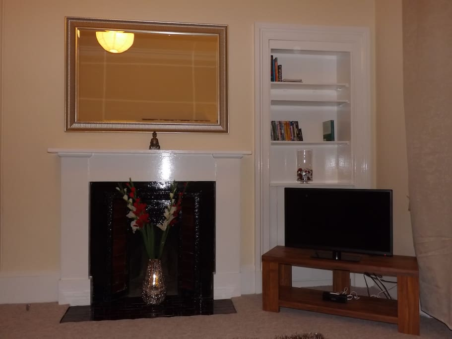 Living room with large freeview TV and original fireplace