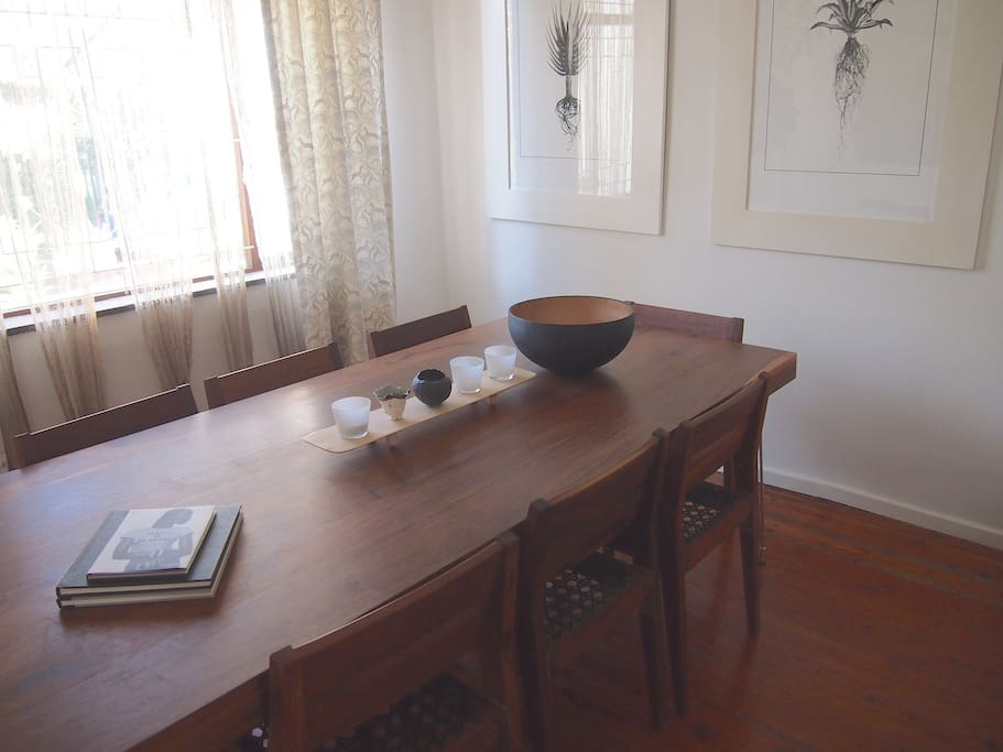The intimate dining room hosts a generous wooden table and comfortable chairs.