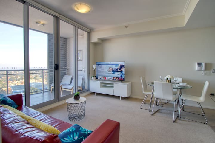 Living room with smart TV, Netflix, YouTube & sunblock blinds and sofa bed.