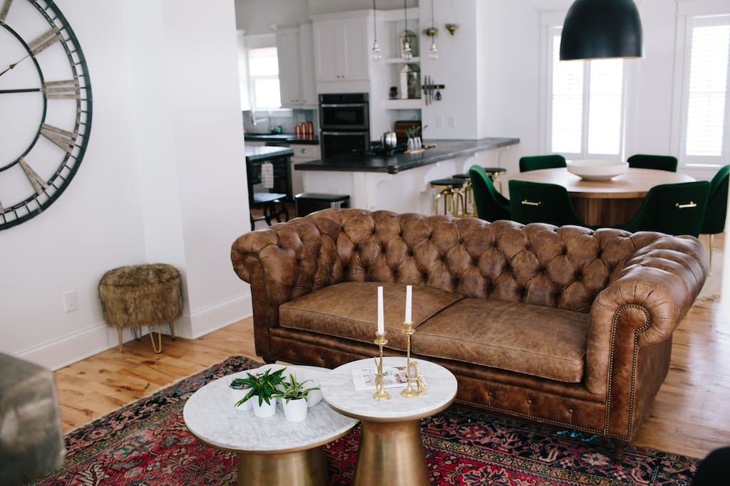 The living room includes a leather couch