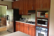 Kitchen with a gas 4 burner cooktop, oven and full refrigerator.