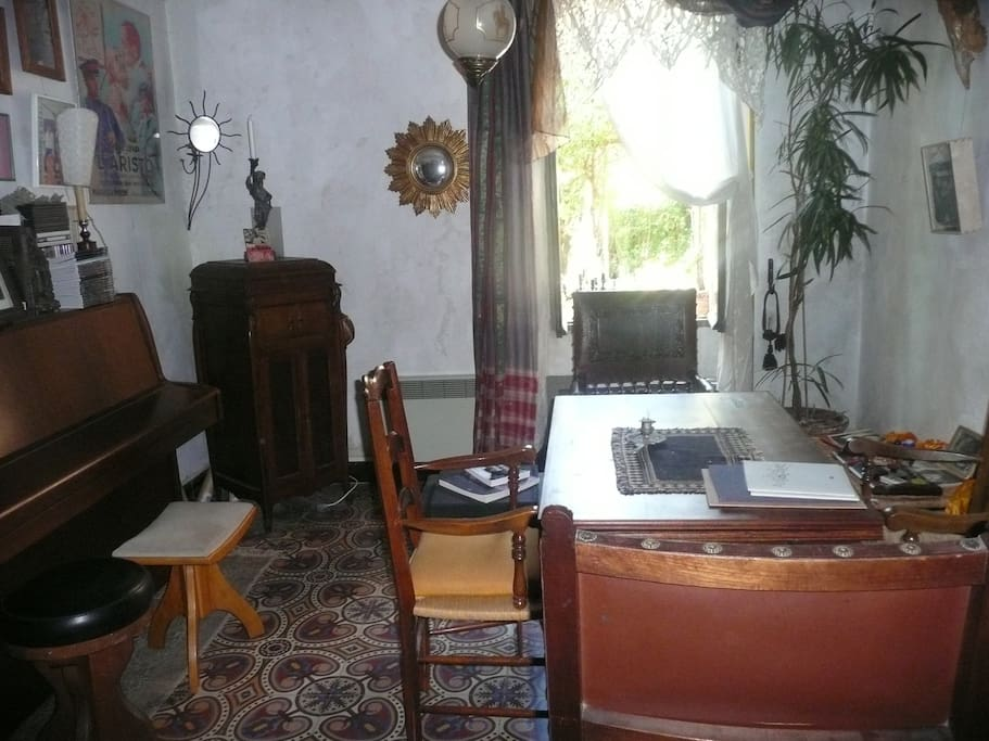 the piano room (bedroom n°2) has a large desk ; also looks out onto the patio (note the 1890 cement tiles)
