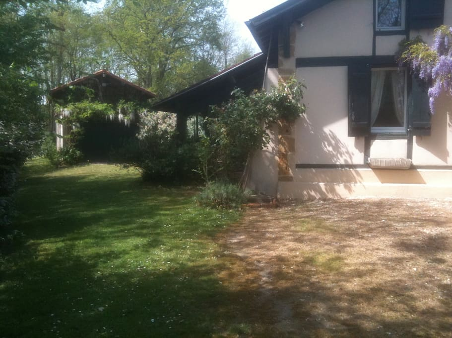 Côté de la maison avec la véranda et la grange