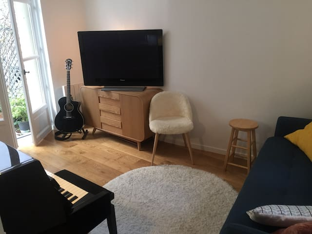 L'espace salon avec son canapé convertible haut de gamme, son piano droit, sa grande télévision... Avec ouverture sur la terrasse