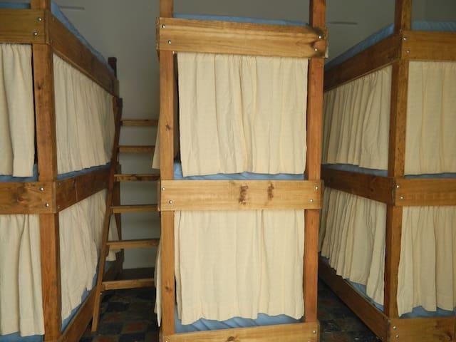 Cama en dormitorio de Hombres Ikali Hostel
