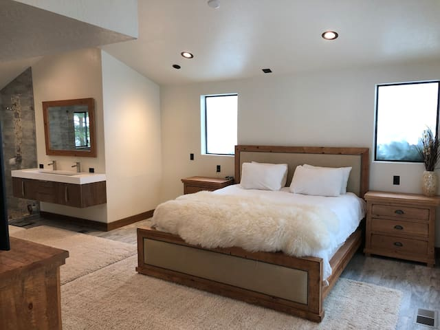 """Brand new master bedroom retreat. Walk through the barn door and enjoy a 75"""" flatscreen TV, king sized bed with heated mattress pad, custom vanity, shower, tons of mirrors and more!"""