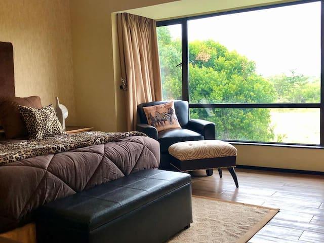 Master bedroom, en suite. Queen size, ottoman and reading chair. Views of Mt. Kenya