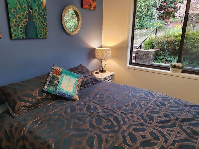 Guest room with queen size bed overlooks the garden
