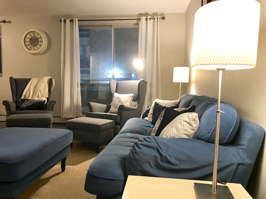 """Spacious living room,  full couch, two chairs and ottomans, matching """"coffee table"""", desk, lamps, end tables, fluffy pillows and a cozy blanket!"""