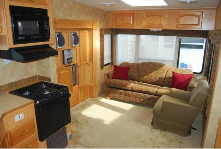 Fully furnished RV nestled in the woods