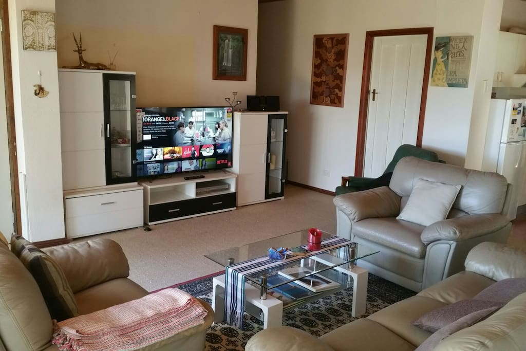 The living room is your place to relax. Comfortable leather lounge. Large 55 inch hd smart TV.  Free access to Netflix and a large selection of DVDs. Playstation 2 with a good game selection for young and old.