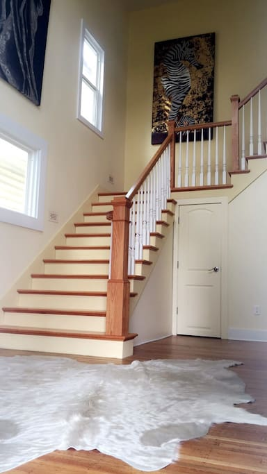 Front entrance gives a warm welcome with a furry white cowhide, and 19foot high ceiling. The beautiful local artwork showcased lines the remodeled stairwell.