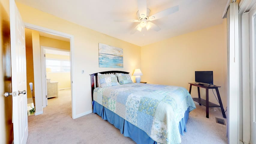 Upstairs sound side bedroom with TV (antenna), super comfortable firm pillow top mattress, wireless fan control and a sliding glass door overlooking the pool, pier and sound.   Shares a bath (tub/shower combo) with twin bedroom across the hall.