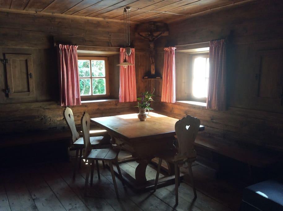 Die traditionelle und denkmalgeschützte Bauernstube (Bild 2/3) mit original Südtiroler Stubenofen, Schlafcouch, 2 Tischen, Stühle und Flatscreen-TV