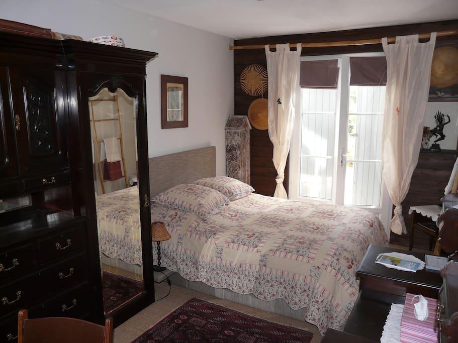 Chambre avec un lit double, accès par la porte vitrée à la terrasse et au jardin