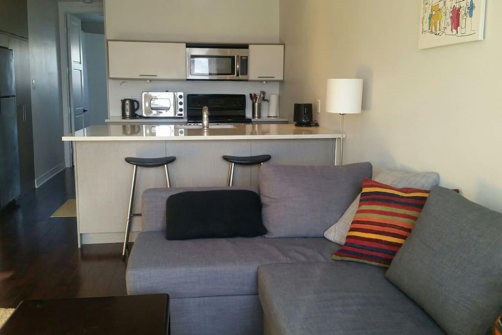 Cuisine ouverte et équipée, espace déjeuner-dîner, salon comfortable et lumineux/Open kitchen fully equipped, dining area, cozy and bright living room