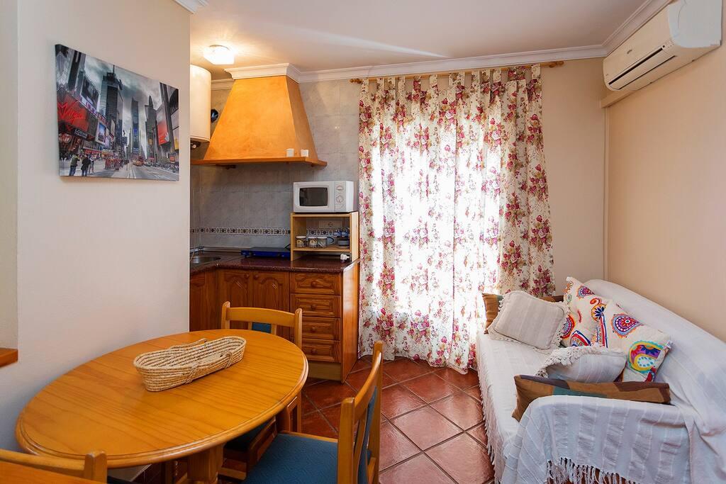 Zona abierta de salón, cocina, comedor, con vistas a la calle.