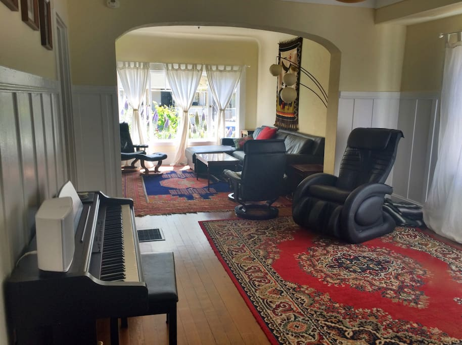 Living rooms with piano and massage chair.