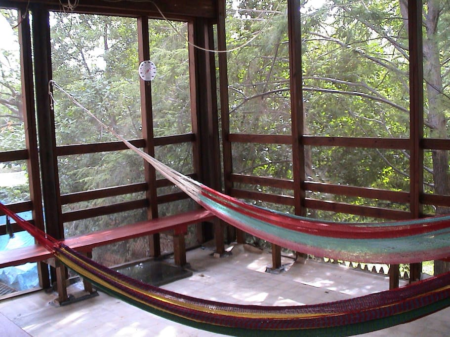 Chill on the screened porch that faces the park and garden.  Hammocks, coffee table, and plenty of seating all included.