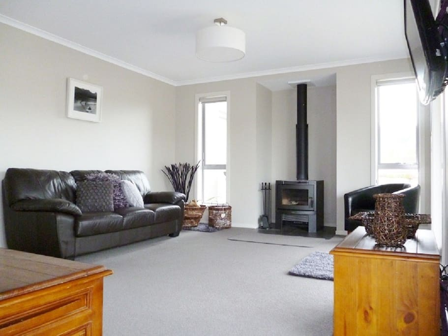 Large sitting room with log burner and air conditioner. AppleTV and DVD, with reading and dvd libraries. Plenty of comfortable seating.