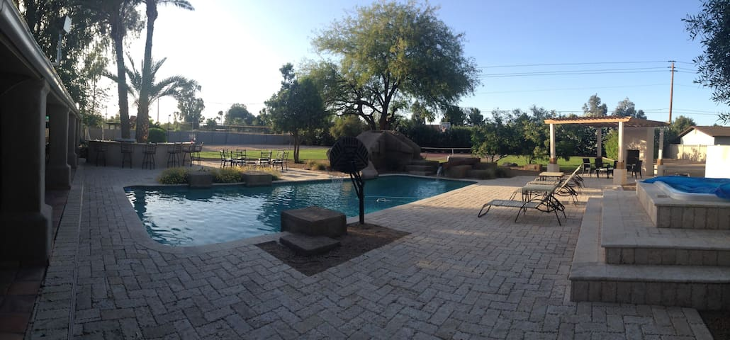 Backyard has hot tube , pool , fire pit , bar, ping pong , pool table and more