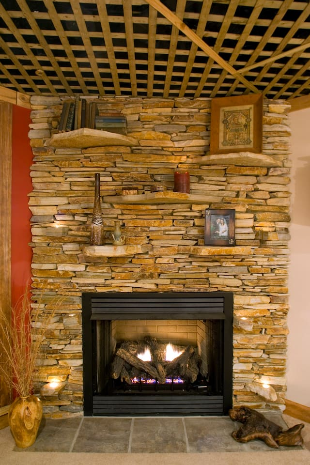 Gas fireplace with real stone shelves and tea-light holders makes for a cozy evening.