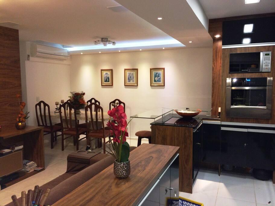 Cozinha americana com cooktop inducao, forno eletrico, armarios e vista da sala de jantar