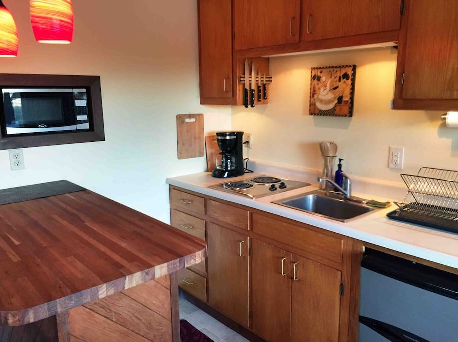 Cherry wood chopping block counter, recessed microwave, and soft lighting in the fully equipped kitchenette