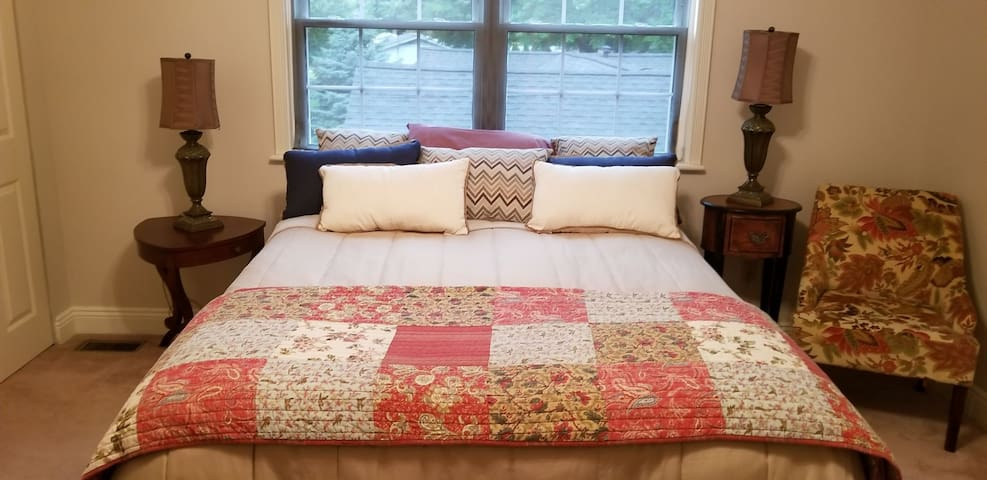 """Second floor, """"First Mates"""" guest suite. Queen bed, ample closets, and shoe racks.  Ample lighting and ceiling fan. Two side tables with lamps, and two reading chairs.  A Vintage antique dresser with vanity mirror and two vanity lamps."""