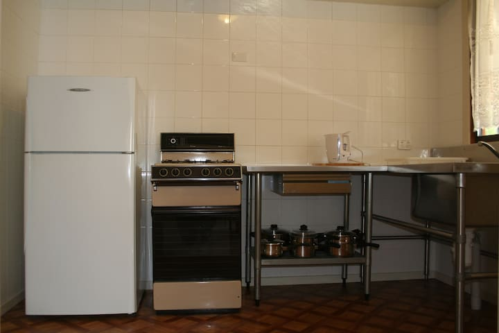 Tiled kitchen with stainless steel benches and gas cooking