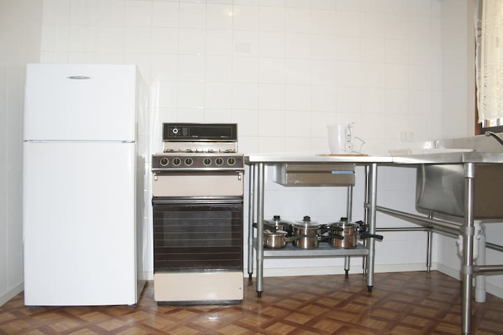 Tiled kitchen with stainless steel benches and gas cooking.