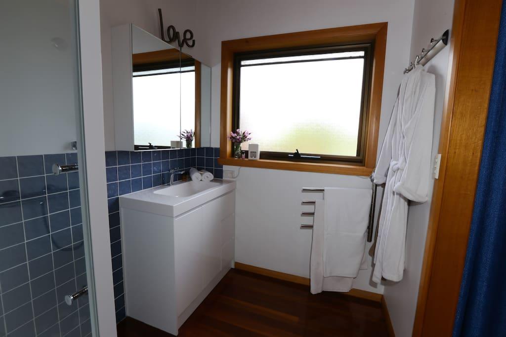 Modern bathroom with heated towel rails, bathrobes and toiletries.
