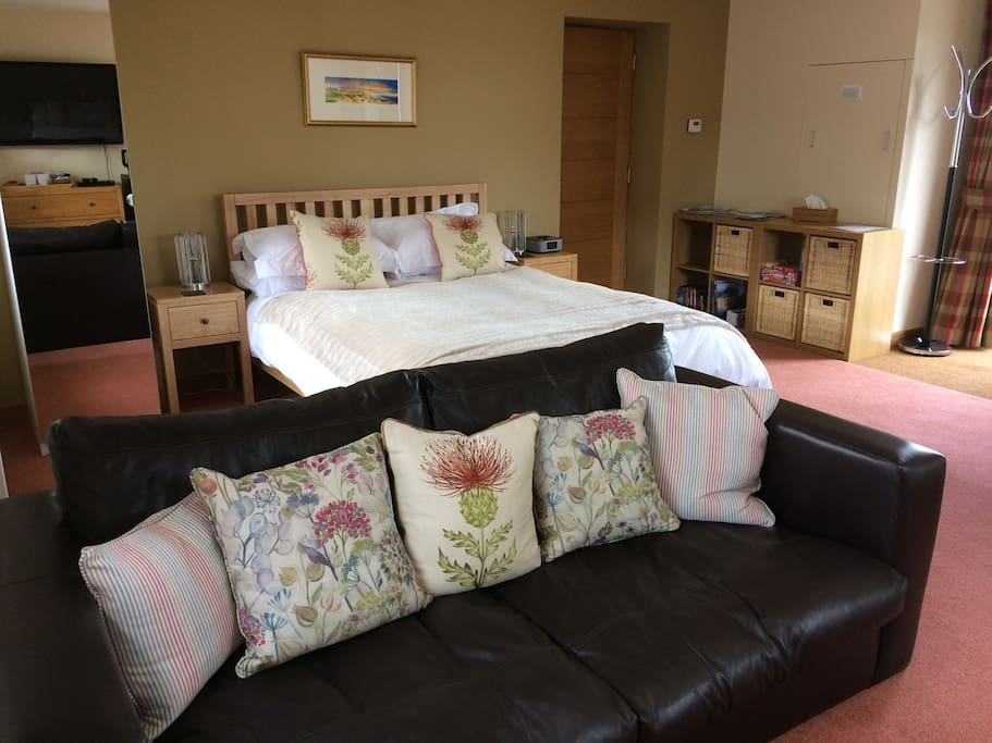 Room with wardrobe, sofa, king size bed. A nice room to relax in after a busy day sight seeing in the Highlands.