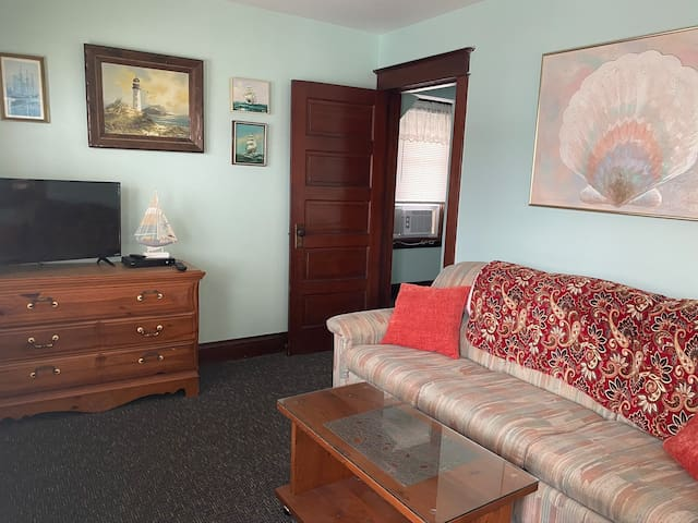Unit 1 living room with cable TV, pullout queen couch, ceiling fan and view of Boardwalk.