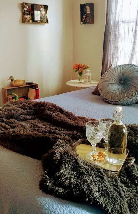 Bed with down comforter and many luxury bedding and pillows.