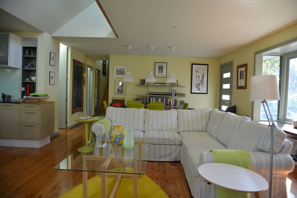 Light filled living room with generous comfortable couch and six seater dining table