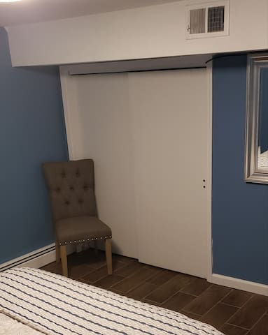 Chair and closet located in bedroom.