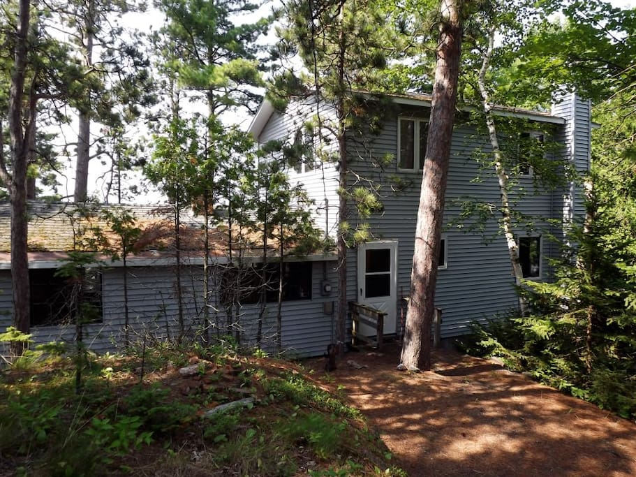 House is tucked in the woods but immediately adjacent to the road.