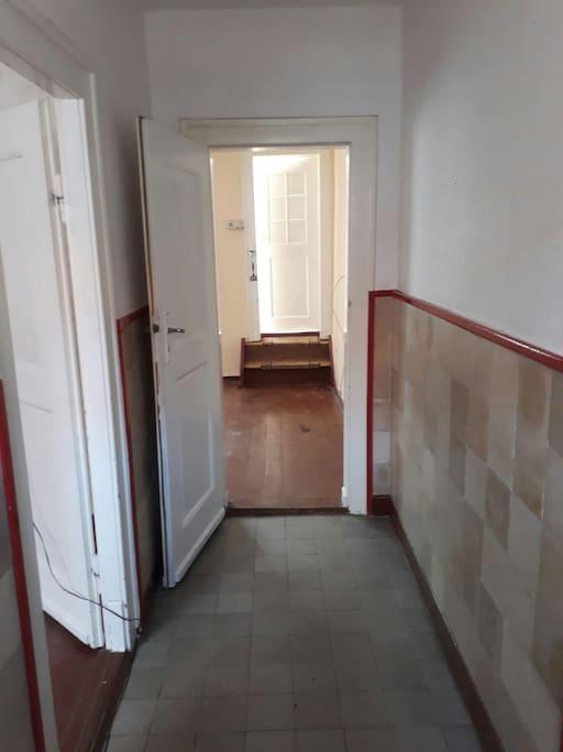 Flur; links Raum 1, geradeaus Raum 2, weiter geradeaus Küche, rechts der Kamera Haustür