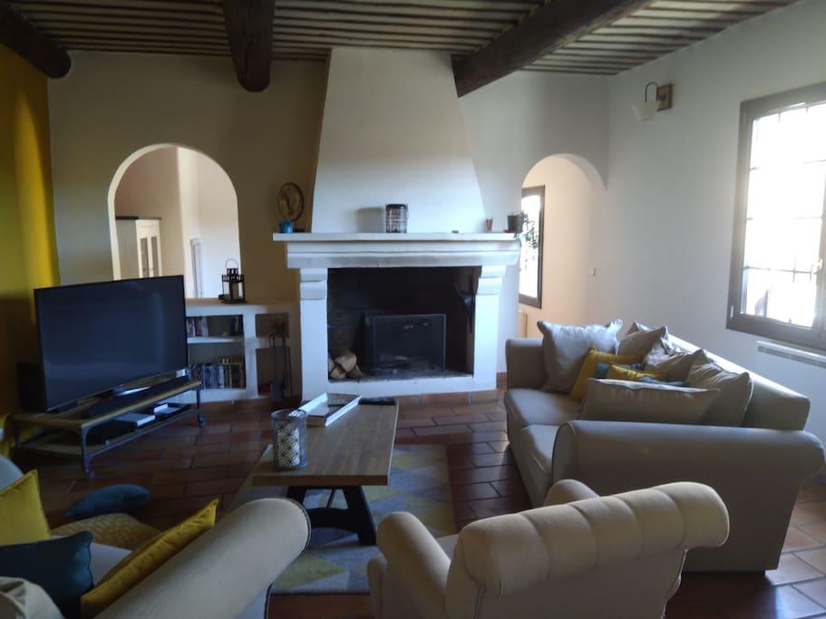 Salon chaleureux avec cheminée  ancienne et plafond à  la française.