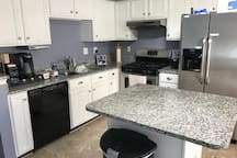 Kitchen with granite countertops, coffee maker station, sink with embedded drying rack, Echo Show, dish washer, gas oven, toaster, Echo Show, and labeled drawers. Bread maker and wheat grinder are available upon request. Guests may use the kitchen freely, but they are expected to clean up after themselves.