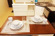 We provide for basic kitchen needs like microwave oven, rice cooker, oven toaster, water heater. We  also have a set of dining utensils good for two persons. We have a small but functional (bigger than personal) refrigerator.