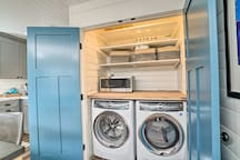 Open the blue French doors to reveal full-sized laundry machines.
