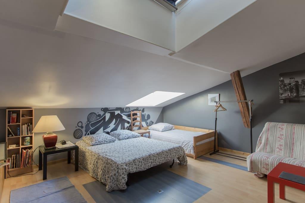Une chambre spacieuse avec 2 lits d'1 personne, 1 lit 2 personnes et un futon