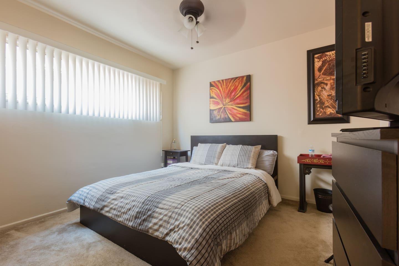 Cozy bed in well lit room.