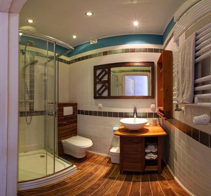 Minimalistyczna łazienka, naturalne drewno sprawia wrażenie podgrzewanej podłogi, szklana kabina prysznicowa, solidna deszczownica Grohe